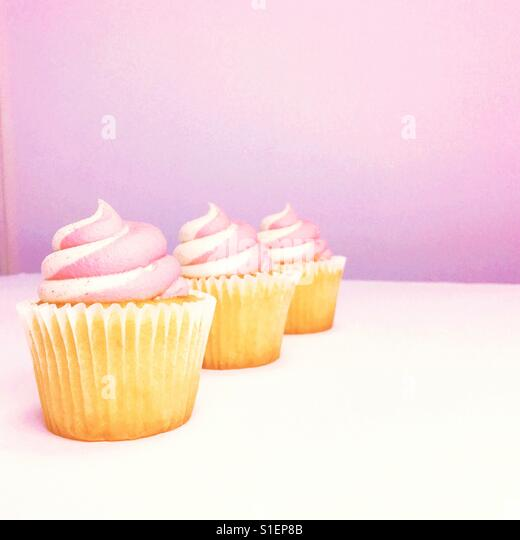 Three vanilla strawberry cupcakes. Space for copy. - Stock Image