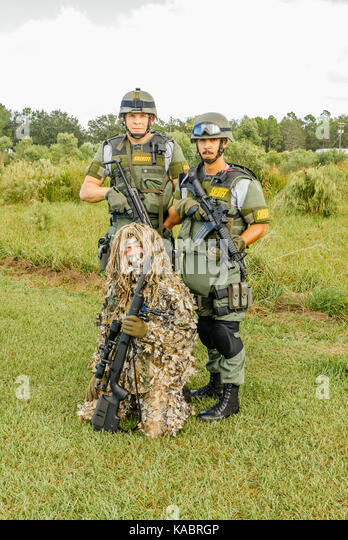 Three members of the Hillsborough County Sheriff's Office SWAT team, with full gear and one in a ghillie suit - Stock Image