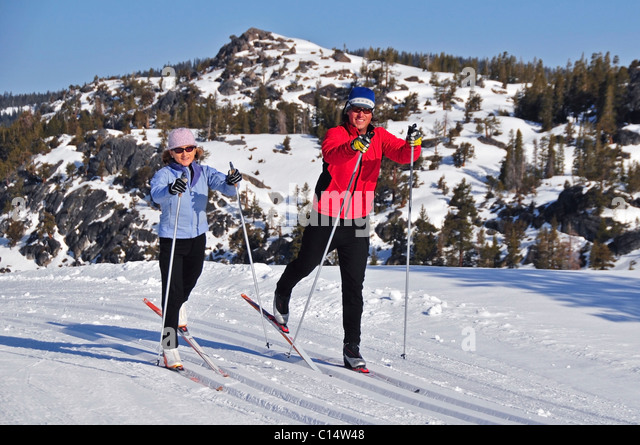 A man and woman cross country ski at Kirkwood Mountain Resort, California. - Stock Image