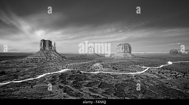 Black and white photo of the Monument Valley with car lights trails at night, USA. - Stock Image