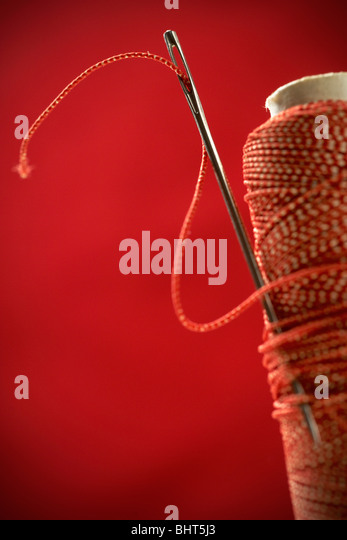 macro shot of an eye of a needle agaist red background - Stock Image