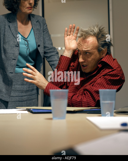 40 s male under threat from 40 s female in office - Stock Image