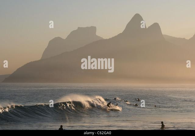 Surfers at sunset at Arpoador Beach, Rio de Janeiro, Brazil - Stock Image