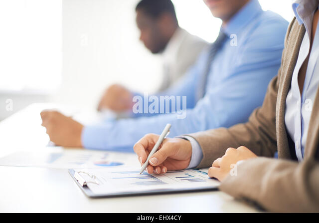 Row of people making notes on spreadsheet - Stock Image