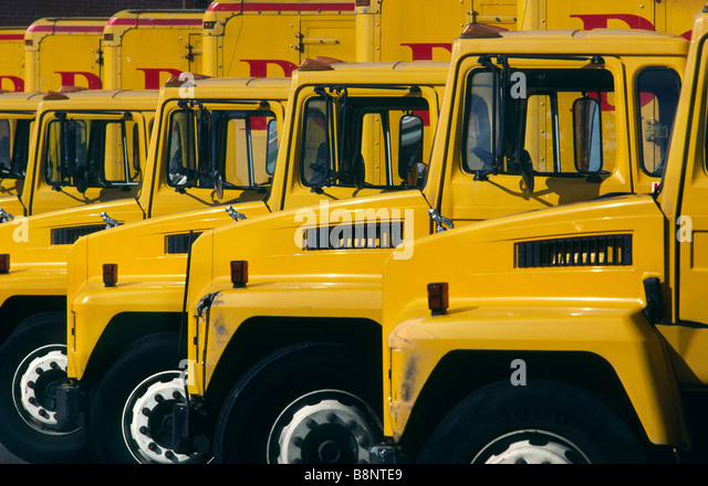 A fleet of yellow delivery trucks - Stock Image