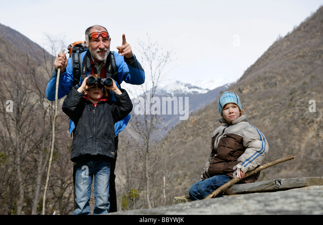 Grandfather shows his grandchildren something with his binoculars - Stock Image