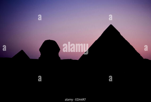 The Great Sphinx and two of the three ancient pyramids at Giza on the outskirts of Cairo, Egypt, are silhouetted - Stock Image