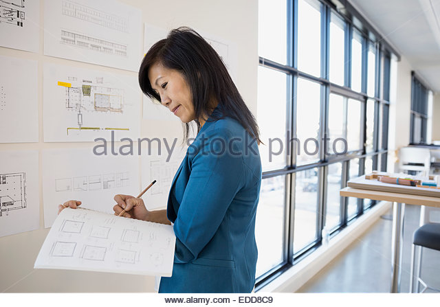Architect drafting plans at wall - Stock Image
