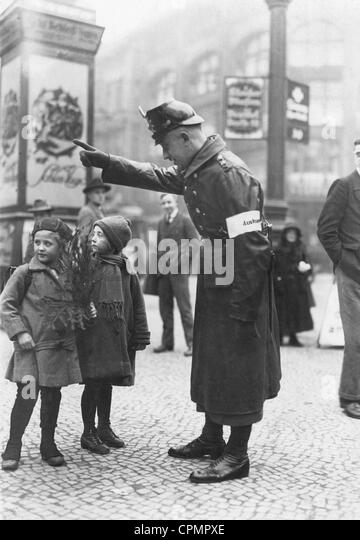 A policeman shows the way to children, 1923 - Stock Image