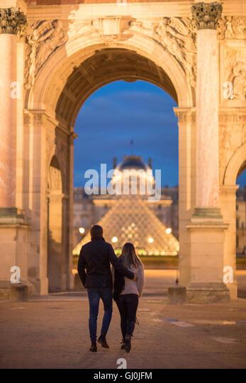 a couple at the Arc de Triomphe du Carrousel & Palais du Louvre at dusk, Paris, France - Stock Image