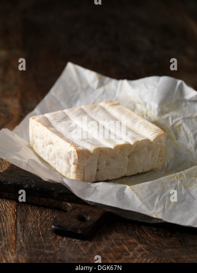 Still life with whole pont l'eveque cheese - Stock Image