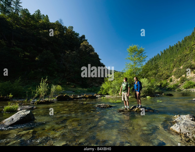 Hikers stranded on rock in middle of river - Stock Image