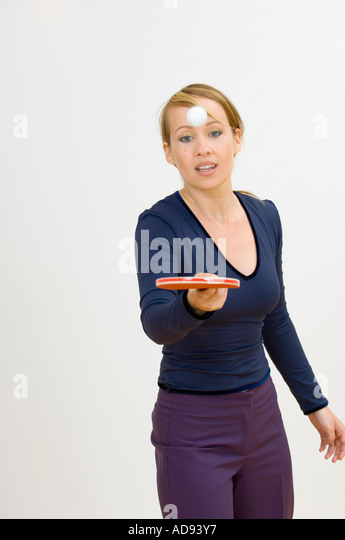 woman juggling a ball with a table tennis racket - Stock Image