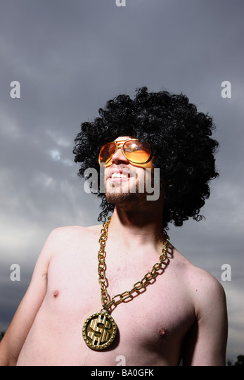 Funny guy with afro wig glasses and bling - Stock Image