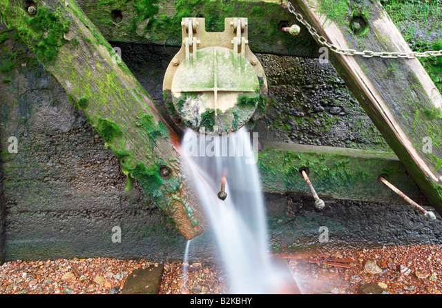 Sewage overflow outlet pouring into the river Thames, London city, England, UK. - Stock Image