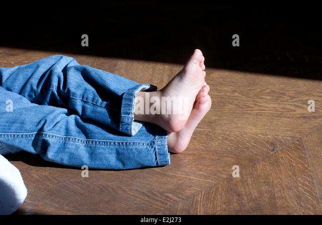 Barefoot child sitting on floor, low section - Stock-Bilder