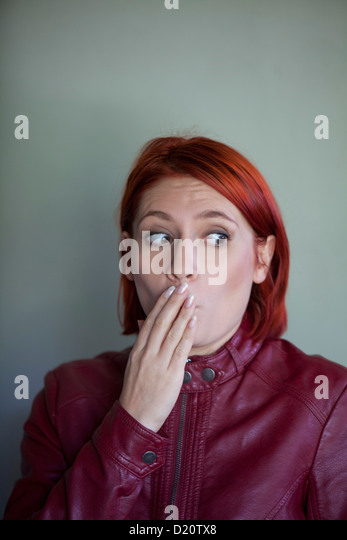 woman with hand on mouth - Stock Image