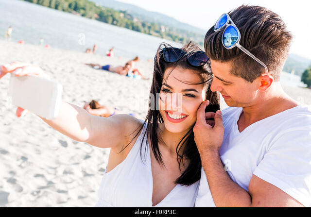 Beautiful couple taking a selfie of themselves on a summer day - Stock Image