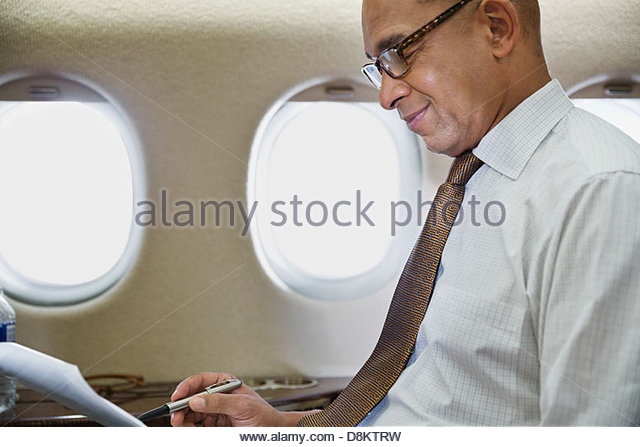 Businessman reading documents in airplane - Stock Image