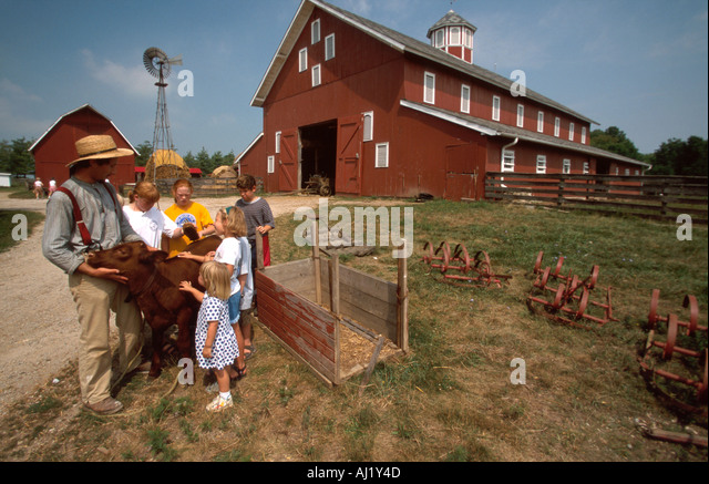 Ohio Pickaway County Slate Run Living Historical Farm interpreter calf young visitors barn beyond - Stock Image