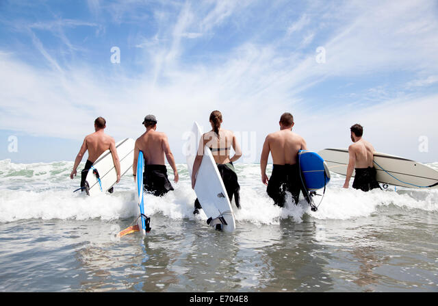 Rear view of a group of male and female surfer friends wading into sea with surf boards - Stock-Bilder