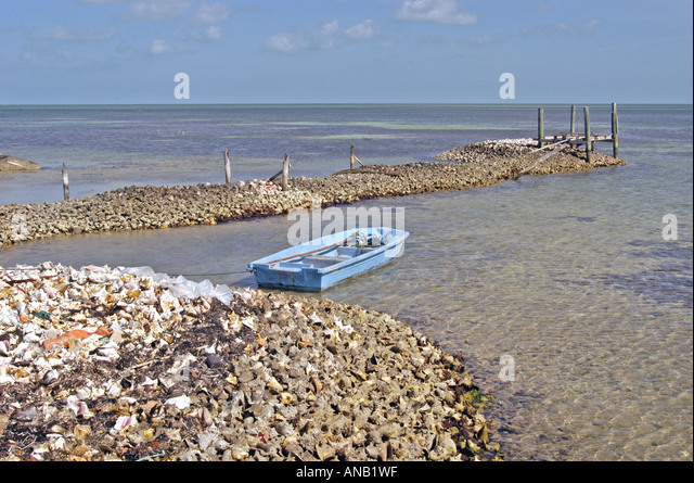 Bahamas Bahamian mounds of conch shells old blue boat - Stock Image
