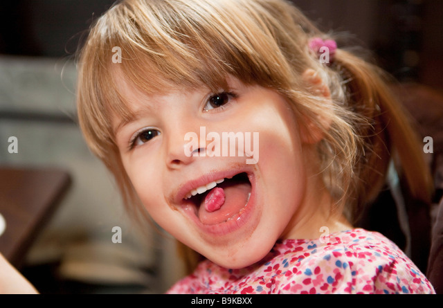 Girl with pink candy on tongue - Stock Image
