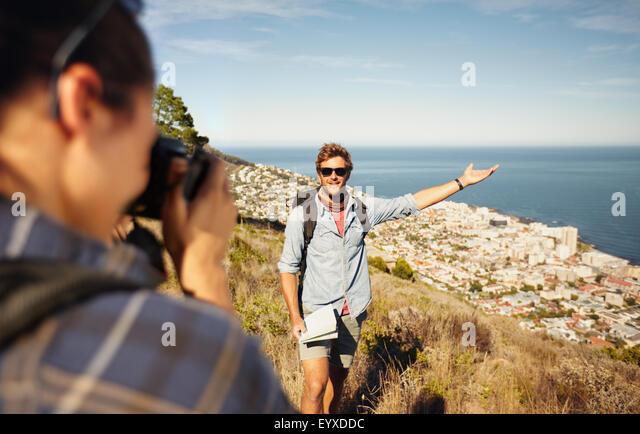 Outdoor shot of tourist couple enjoying nature and taking photo. Woman taking picture of boyfriend showing something - Stock-Bilder