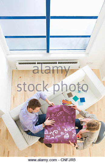 Couple looking at wallpaper sample in living room - Stock Image