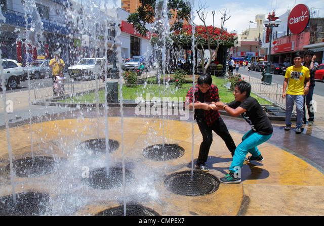 Peru Tacna Avenida San Martin Plaza de Armas interactive water feature fountain water jet spout Hispanic teen boy - Stock Image