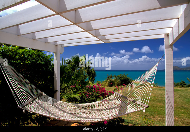 tropics, white rope hammock, no people, romantic tropical setting, blue sky background, green water, colorful flowers, - Stock Image