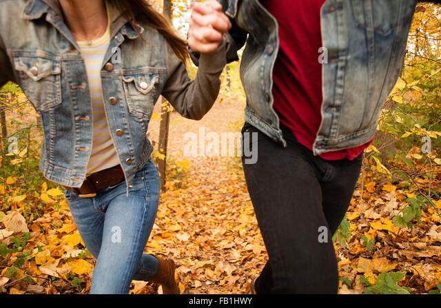 Cropped shot of romantic young couple running through autumn forest - Stock-Bilder