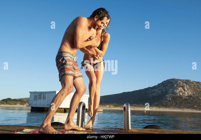 Young couple in bikini and swim trunks playing on sunny summer ocean dock - Stock-Bilder