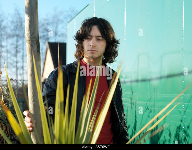 Young man in red and black leather jacket standing amongst a spikey plant - Stock Image