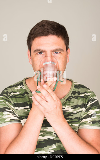 Stressed man in camouflage shirt holding oxygen mask to help him breathe - Stock Image