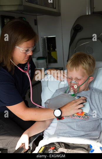 Female paramedic assisting young male patient in back of ambulance. - Stock Image