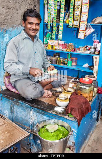 India Asian Mumbai Dharavi 60 Feet Road slum man stall vendor lotions sale convenience store - Stock Image