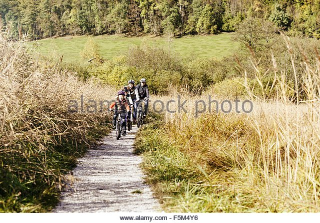 Front view of family cycling on rural path - Stock Image