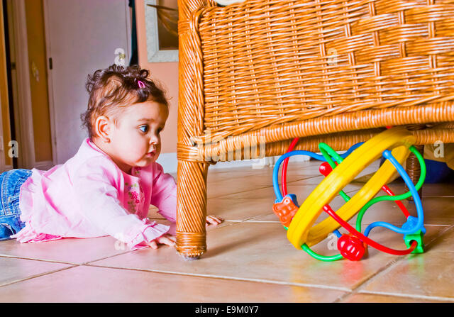 9-month-old Colombian baby girl crawls toward bright colored toy hidden under rattan chair at home. MR  © Myrleen - Stock-Bilder