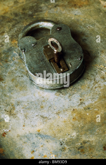 Old fashioned rusty padlock with key over a grungy background - Stock-Bilder