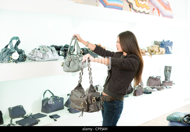 Woman comparing handbags in a shop - Stock Image