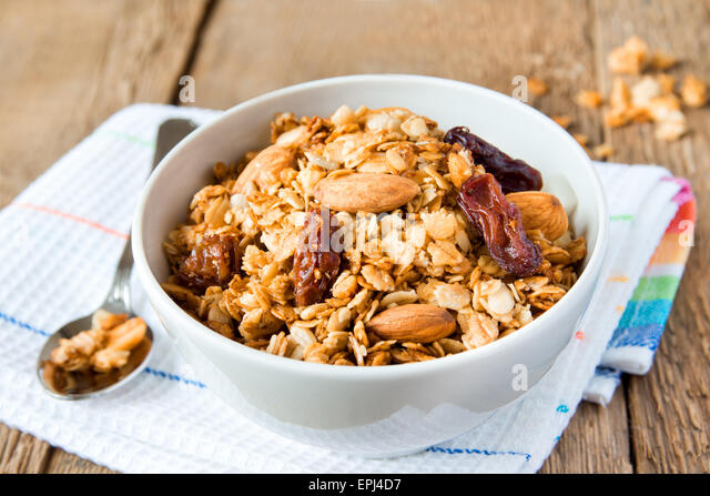 wholegrain muesli for breakfast, with lots of dry fruits, nuts and grains close up, horizontal, on wooden table - Stock Image