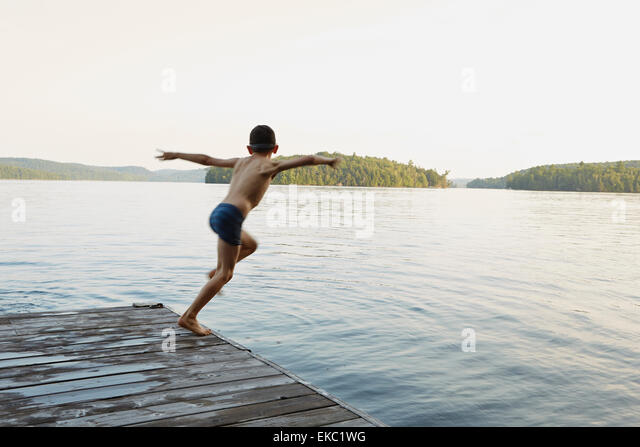 Boy jumping into lake from wooden pier, Ontario, Canada - Stock Image