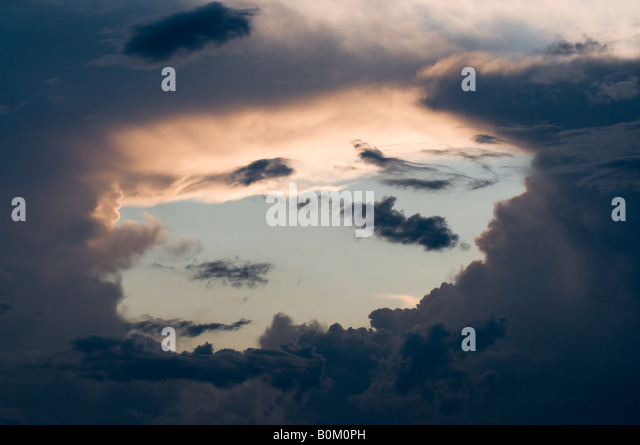 Hole in storm clouds, France. - Stock Image