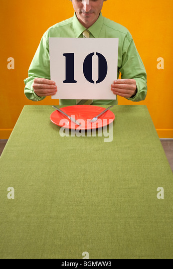 man eating at table holds up 10 sign to rate dinner - Stock-Bilder