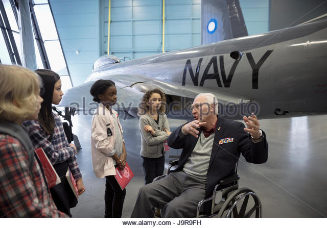War veteran in wheelchair talking to students on field trip at Naval airplane in war museum hangar - Stock-Bilder