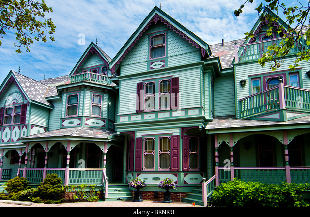 Beautiful big old nostalgic historic wooden green with purple Victorian house building with porch. - Stock-Bilder