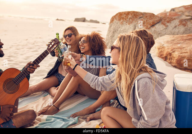 Group of multi-ethnic young people toasting beers on the beach. Group of friends spending time together at the beach - Stock Image