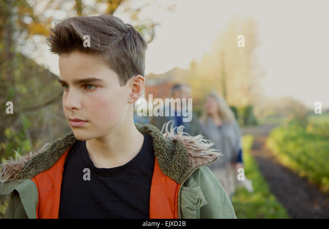 Teenage Boy Walking in Country Road, Parents in Background - Stock Image