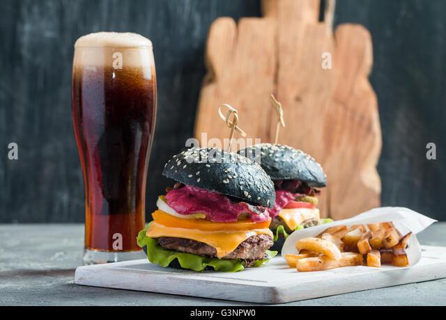 Homemade burger with black bun - Stock Image